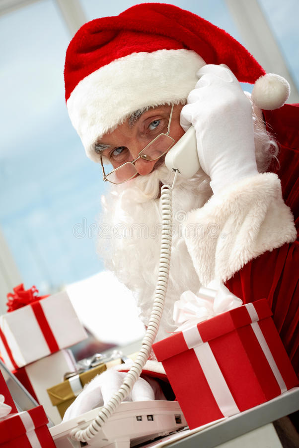 Santa Claus phoning. Photo of busy Santa Claus communicating by telephone royalty free stock image