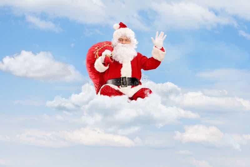 Santa Claus placerade på moln som rymmer en påse och vinka royaltyfria foton