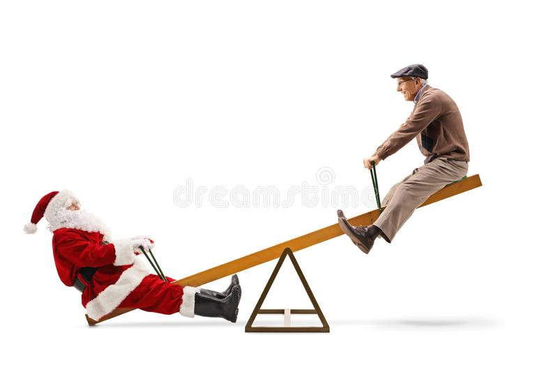 Santa Claus playing on a seesaw with an elderly man stock photography