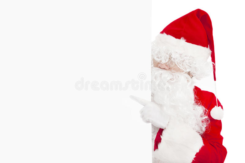 Santa Claus pointing at blank banner. Happy Santa Claus pointing at blank banner royalty free stock photos