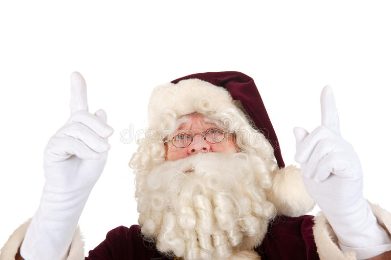 Santa Claus pointing upwards. Santa Claus is pointing upwards to something isolated over white background stock images