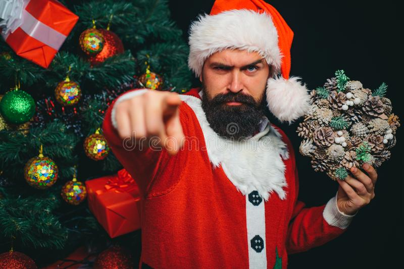 Santa Claus points a finger at the camera. Christmas presents. Bearded young man chose a gift for the new year and stock image