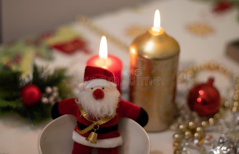 Santa Claus-pop binnen een kom met op een Kerstmistafelkleed met kaarsen royalty-vrije stock fotografie