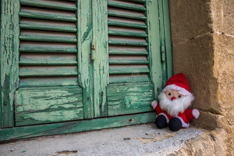 Santa Claus, poppenstuk speelgoed, naast de houten blinden royalty-vrije stock afbeeldingen