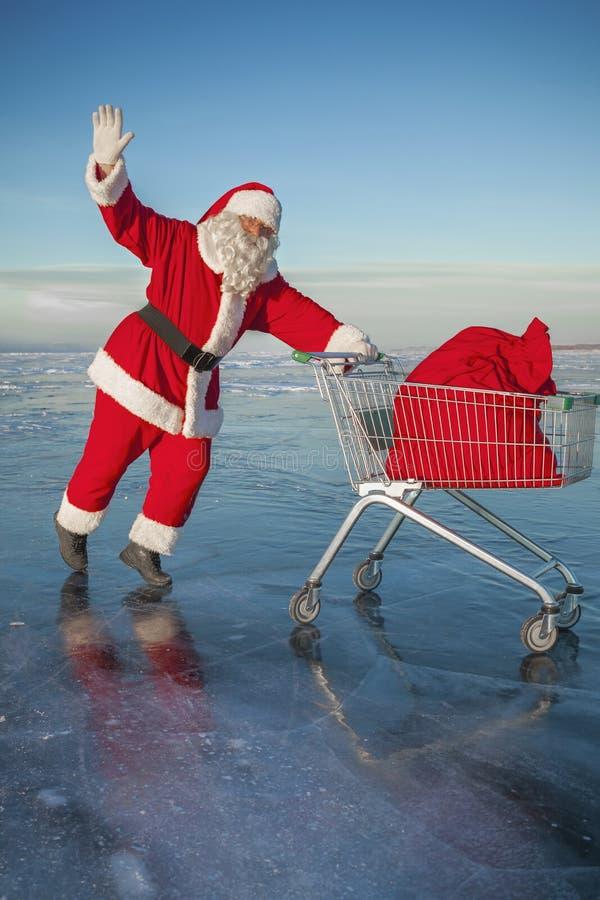 Santa Claus porta un carrello con i regali in un sacco immagini stock libere da diritti