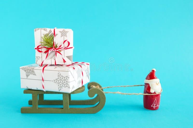 Santa Claus porte le traîneau en bois avec deux boîte-cadeau enveloppés du papier blanc-gris, décoré de la branche de sapin sur l image stock