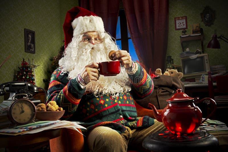 Santa Claus. Portrait of Santa Claus sitting on armchair holding a cup of tea stock photos