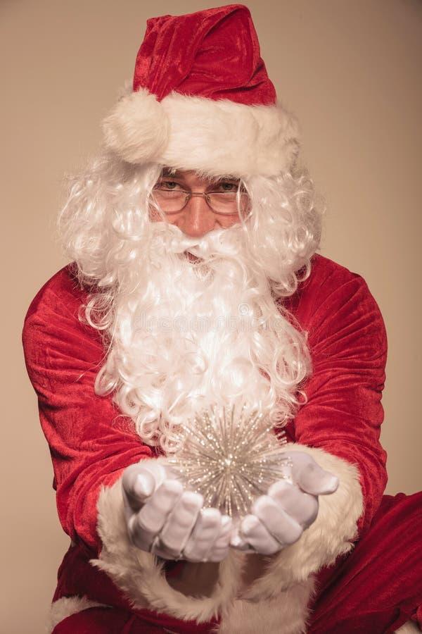 Santa Claus présent un ornement de Noël photographie stock