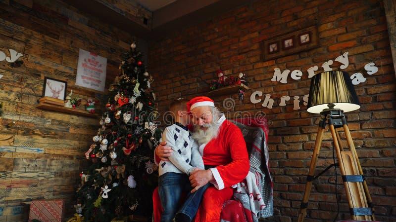 Santa Claus présente le cadeau au boyr heureux photographie stock libre de droits