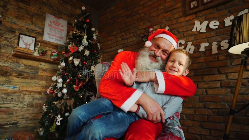Santa Claus présente le cadeau au boyr heureux image libre de droits