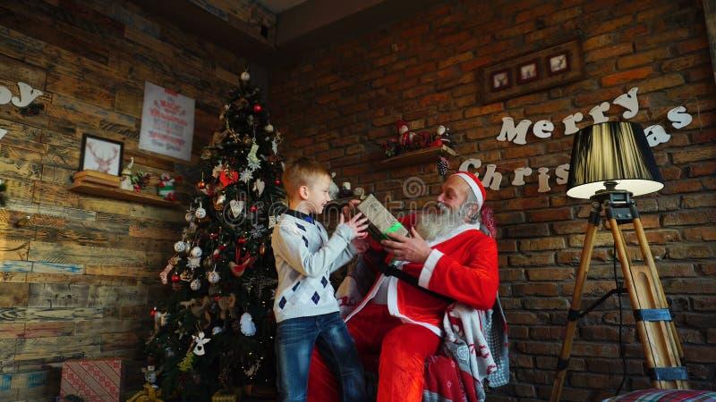 Santa Claus présente le cadeau au garçon heureux photos stock