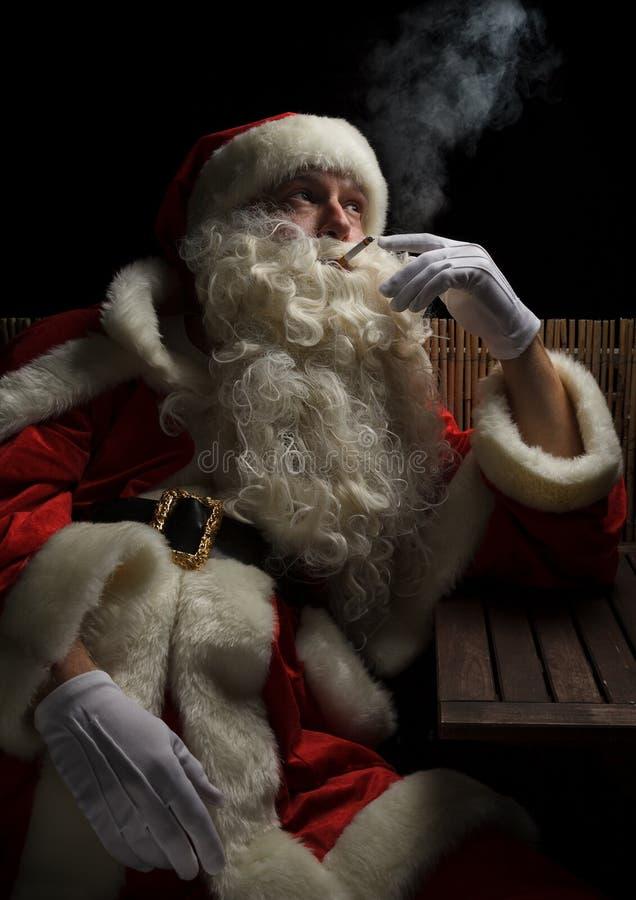 Santa Claus precisa pouca ruptura e fuma um cigarro foto de stock