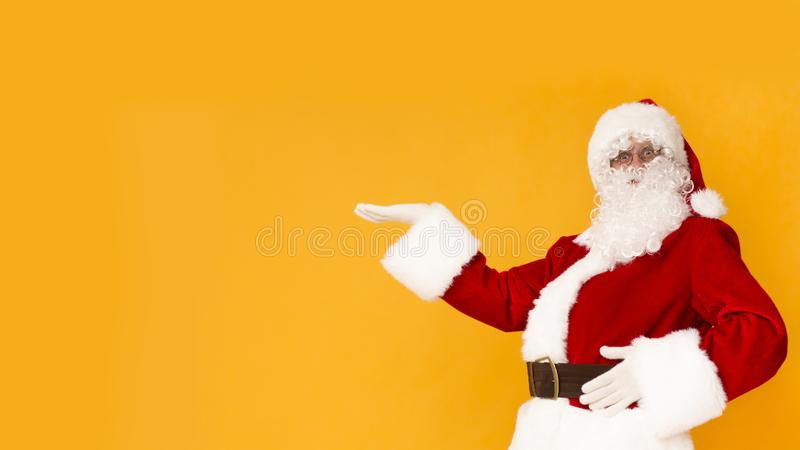 Santa Claus presenting with hand copy space for Christmas text stock photos