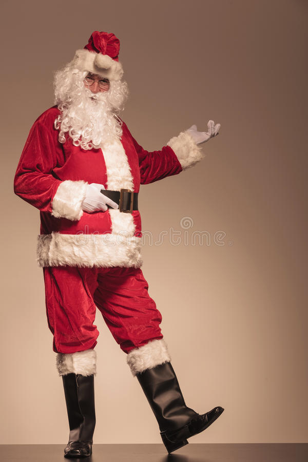 Santa Claus presenting something on his left royalty free stock photo