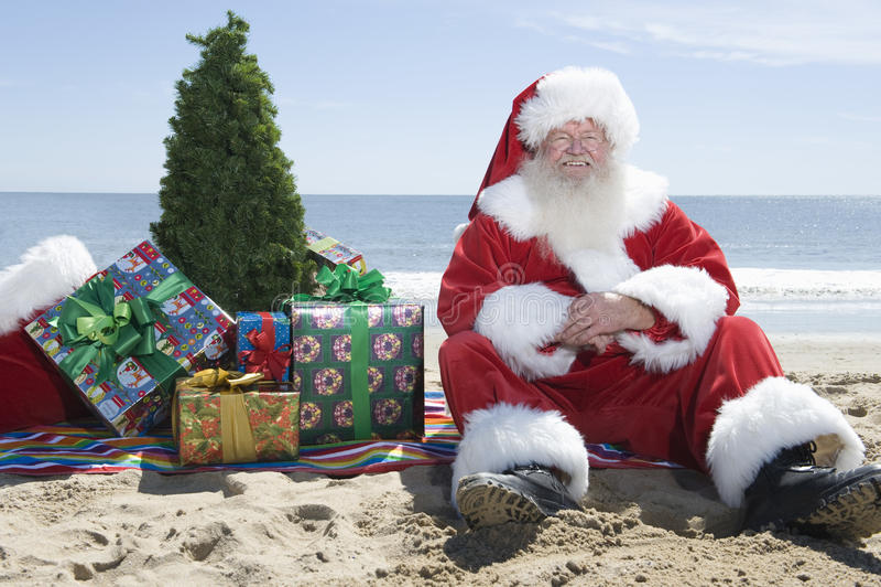 Santa Claus With Presents And Tree que senta-se na praia fotografia de stock royalty free