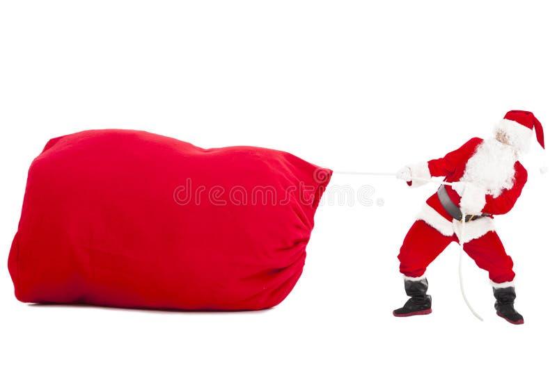 Santa claus pulling a big gift bag. Isolated royalty free stock photo