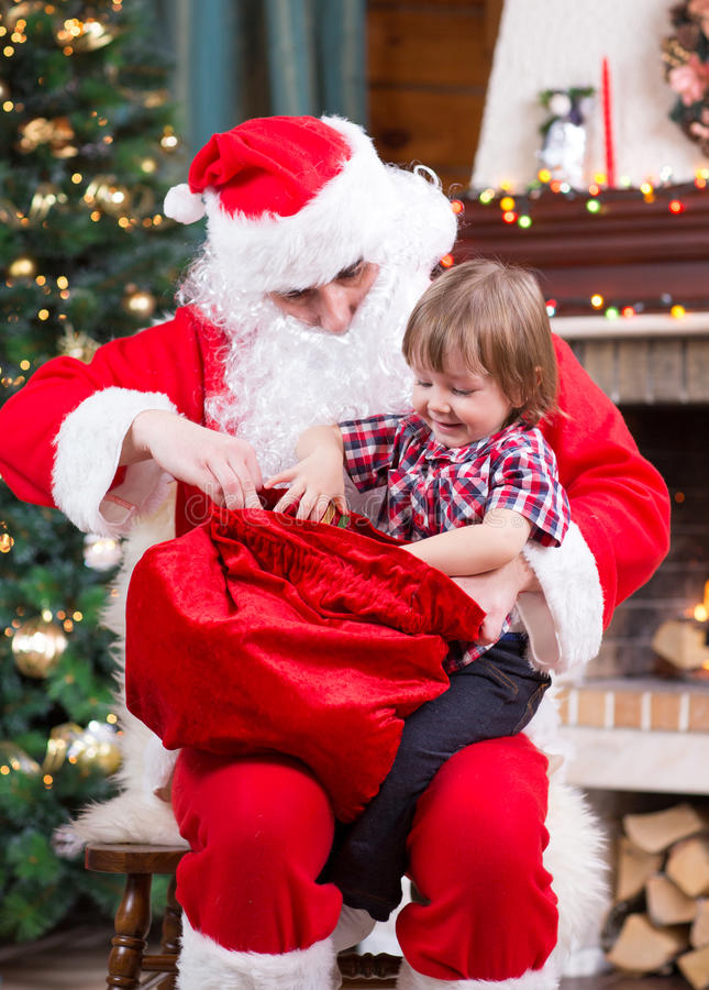 Santa Claus pulls a present out sack to child near royalty free stock photo