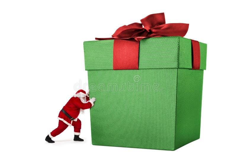 Santa Claus pushing huge bag of gifts royalty free stock photography