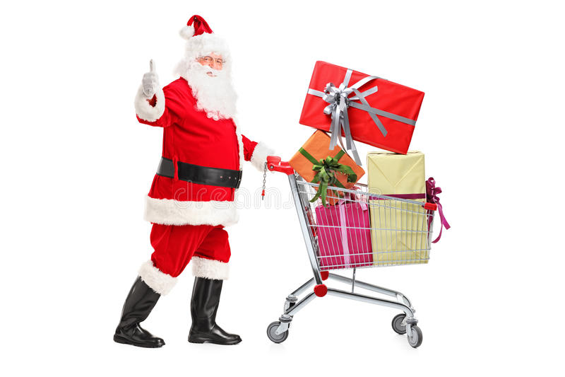 Santa Claus pushing a shopping cart full of gifts. And giving a thumb up on white background stock photo