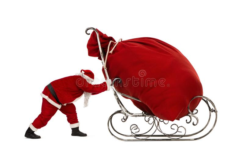 Santa Claus pushing sleigh with huge bag on it. Santa Claus pushing sleigh with huge bag full of christmas gifts isolated on white background royalty free stock photos