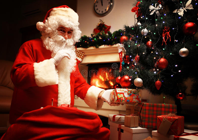 Santa Claus putting gift box or present under Christmas tree at eve night. It's a secret. Don't tell the kids. Xmas and stock image