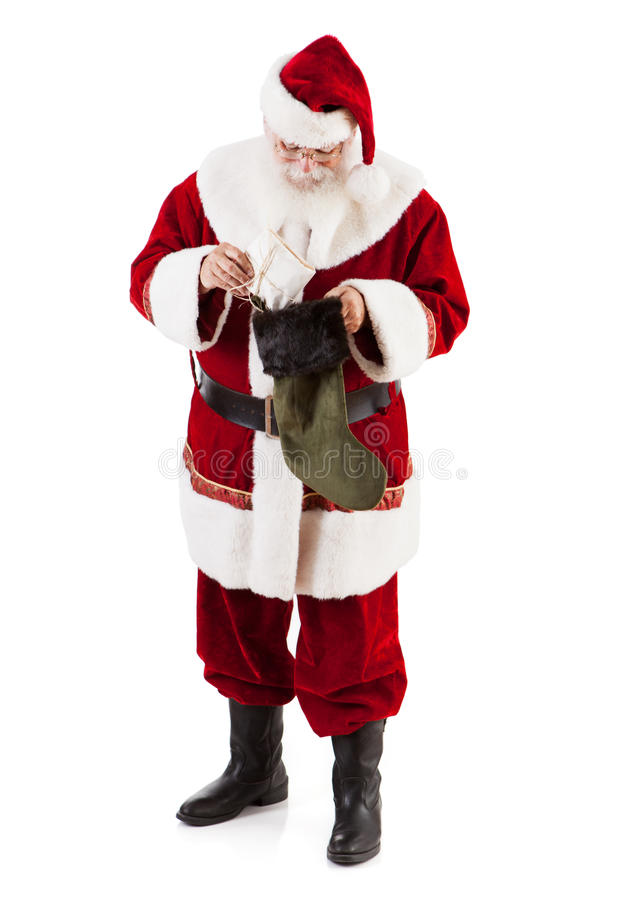 Santa Claus Putting Gift Into Christmas-Kous stock afbeeldingen