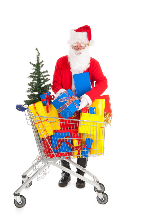 Santa Claus putting a gift in shopping caart. Santa Claus putting a gift in shopping cart full luxury presents and tree royalty free stock photos