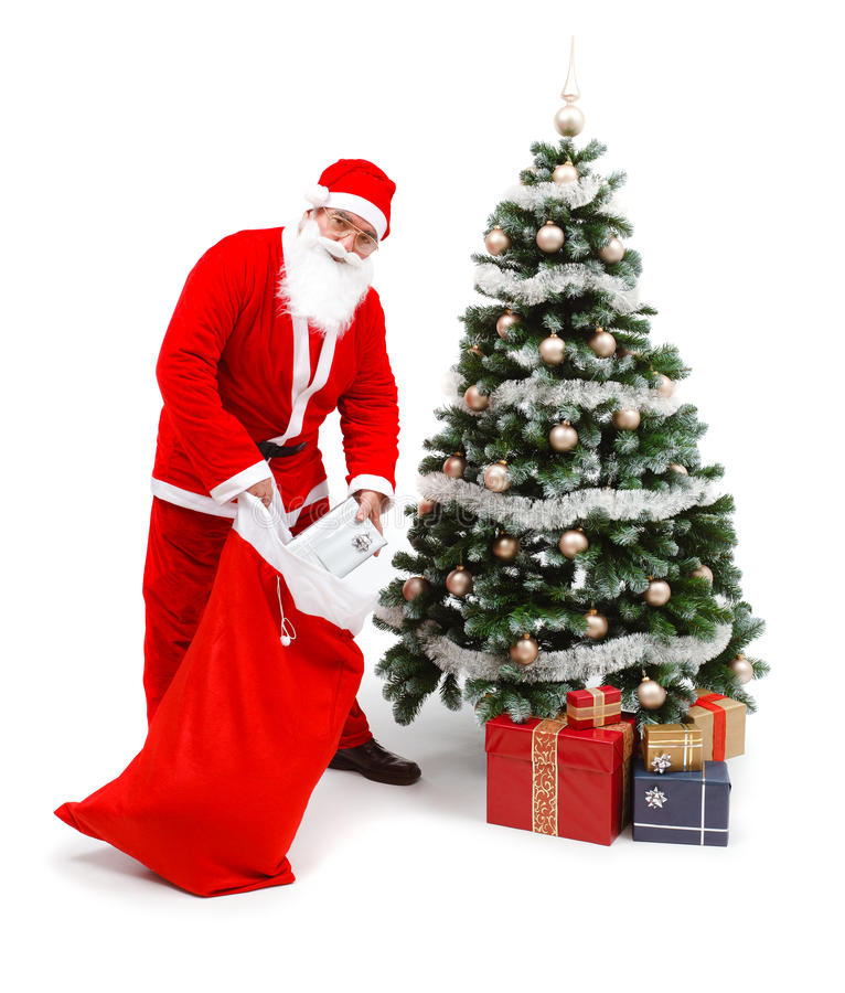 Presents Under The Christmas Tree: Santa Claus Putting Gifts Under Christmas Tree Stock Photo