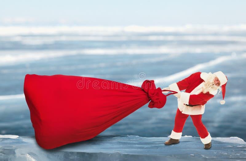 Santa Claus puxa o saco vermelho grande fora fotos de stock royalty free