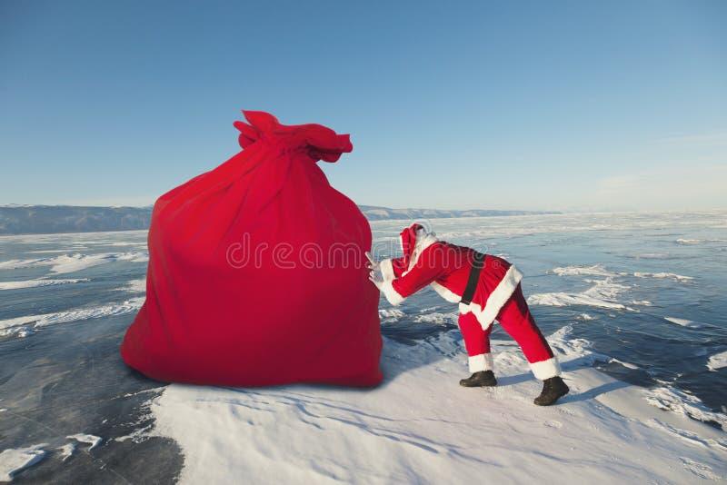 Santa Claus puxa o saco vermelho grande fora fotografia de stock royalty free