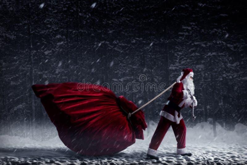 Santa Claus puxa um saco enorme dos presentes fotos de stock
