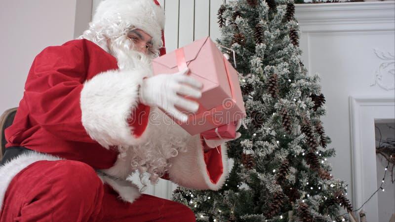 Santa Claus que abre su saco y que pone presentes debajo del árbol de navidad imagenes de archivo