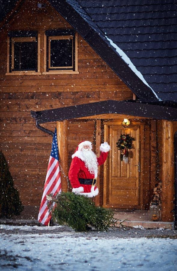Santa Claus que agita y que trae el árbol de navidad en casa imágenes de archivo libres de regalías