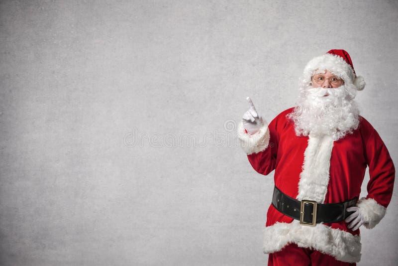 Santa Claus que aponta em uma parede foto de stock