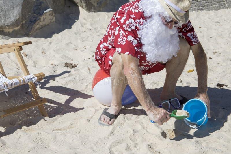 Santa Claus que cava en arena con pálido y pala en la pelota de playa fotos de archivo libres de regalías