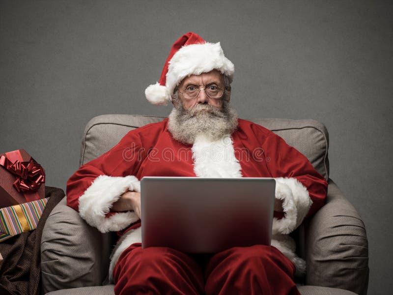 Santa Claus que conecta com um portátil imagem de stock