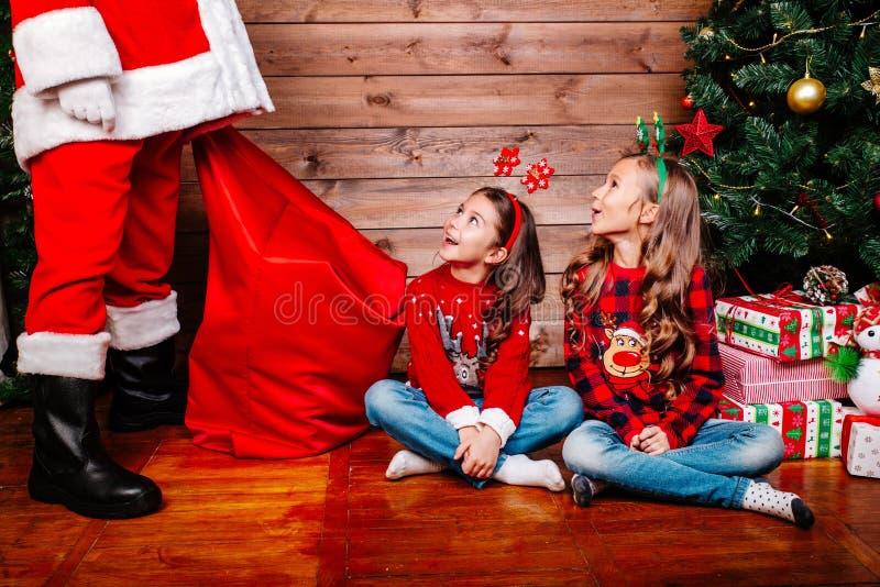 Santa Claus que dá um presente a duas irmãs bonitos pequenas perto da árvore de Natal em casa fotos de stock royalty free
