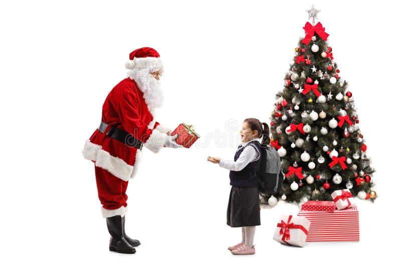 Santa Claus que dá um presente a uma estudante ao lado de um Natal fotos de stock