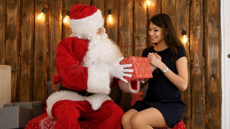 Santa Claus que da un presente agradable envuelto a una mujer joven hermosa en vestido negro foto de archivo libre de regalías