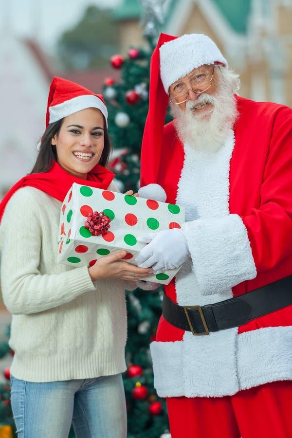 Santa Claus que da un presente a la mujer foto de archivo