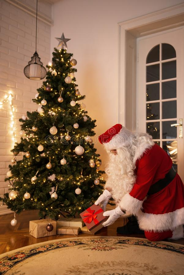 Santa Claus que deixa um presente sob a árvore de Natal fotos de stock