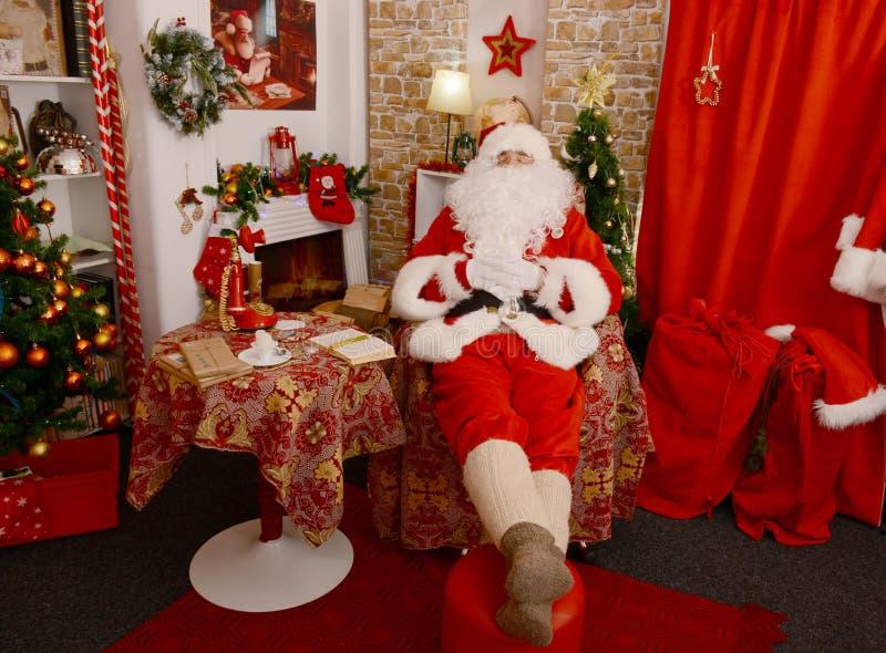 Santa Claus que dorme em sua casa imagem de stock