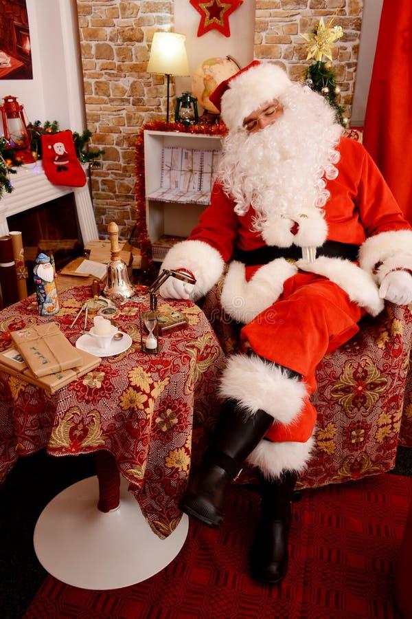 Santa Claus que dorme em sua casa foto de stock
