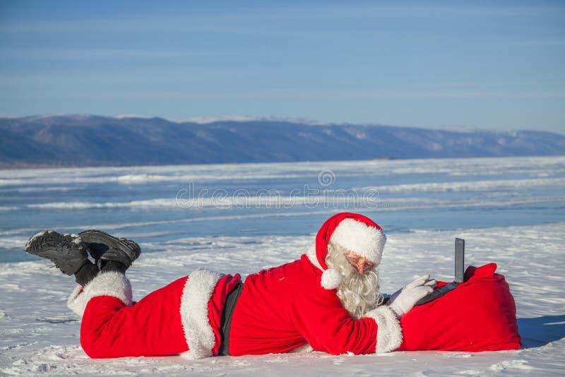 Santa Claus que encontra-se na neve, olhando a notícia do portátil fotos de stock royalty free