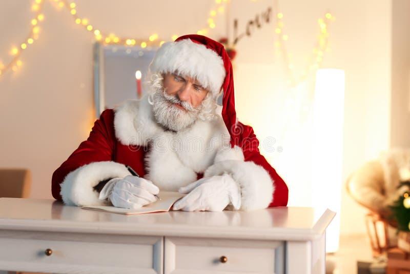 Santa Claus que escreve no caderno ao sentar-se na tabela na sala decorada para o Natal foto de stock