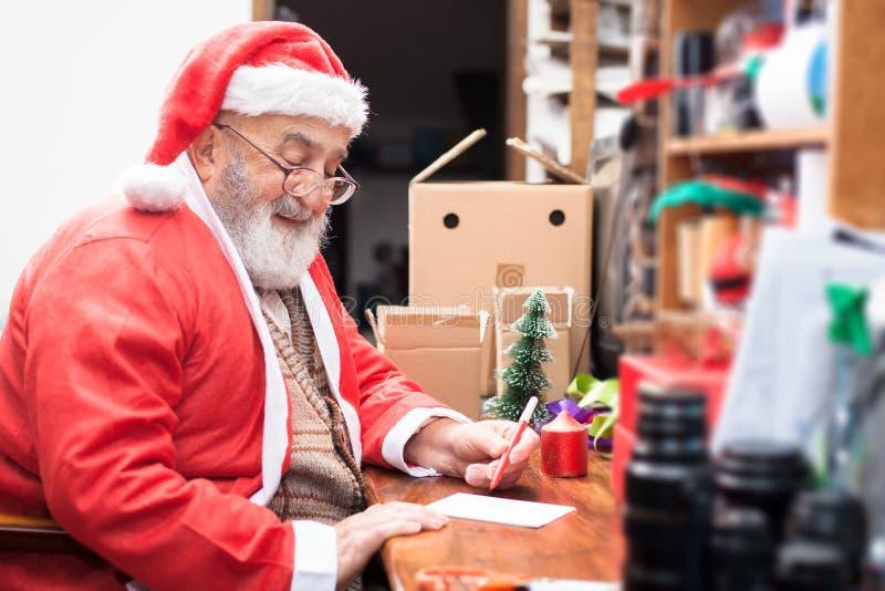 Santa Claus que escreve uma mensagem do presente fotos de stock