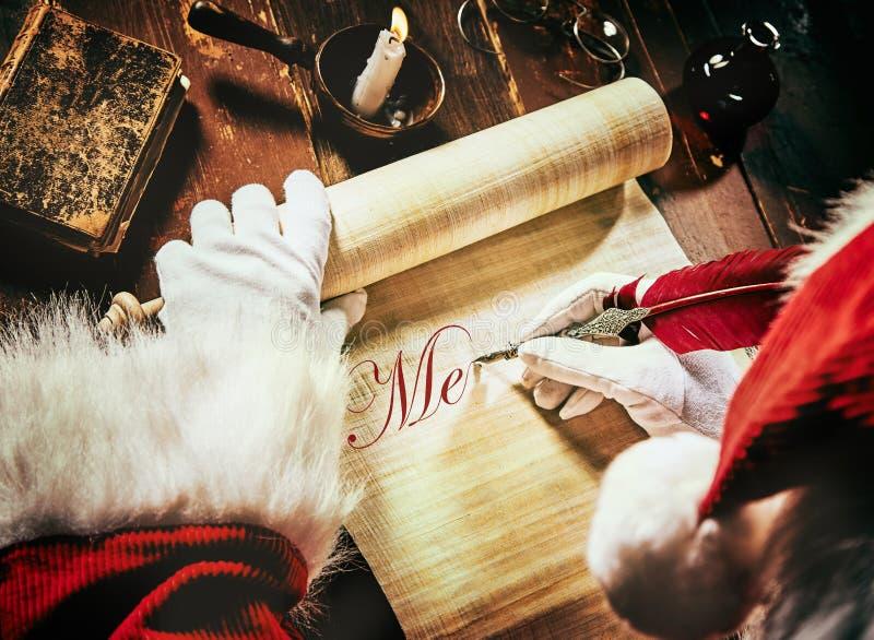 Santa Claus que escribe un saludo de Navidad en una voluta fotografía de archivo