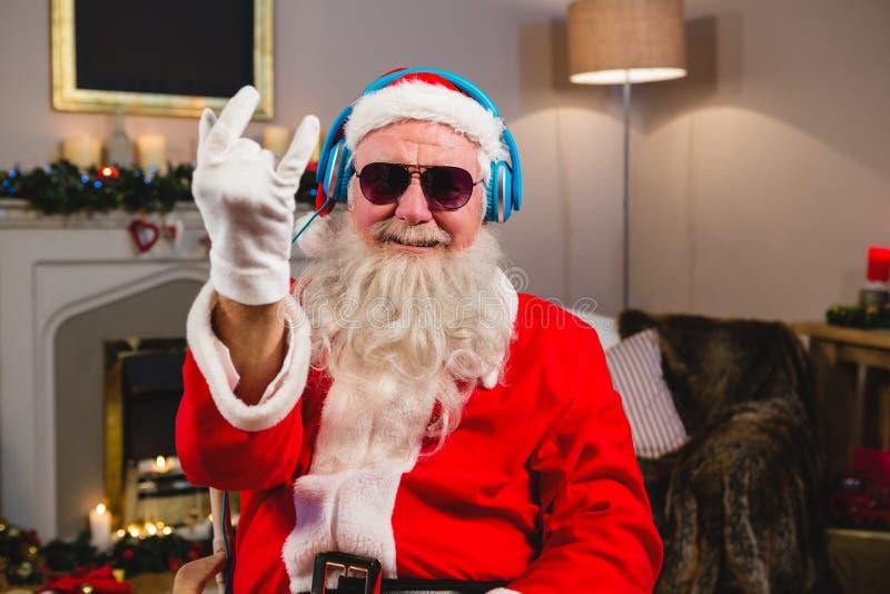 Santa Claus que escuta a música em fones de ouvido em casa foto de stock royalty free