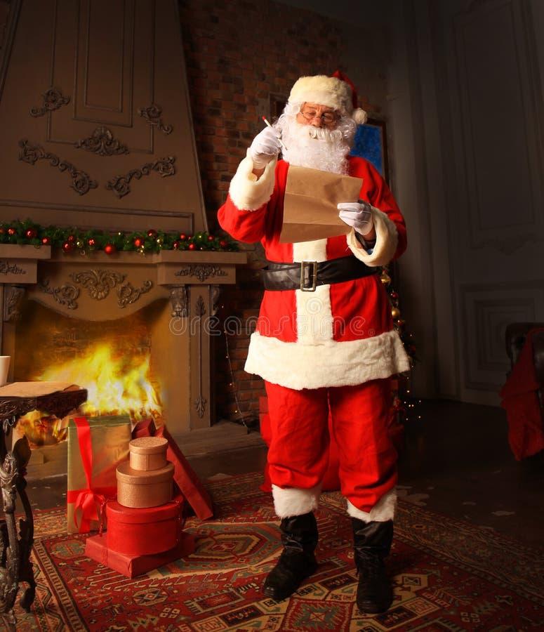Santa Claus que está em sua sala em casa perto da árvore de Natal e do saco grande e que lê a letra ou a lista de objetivos prete imagem de stock