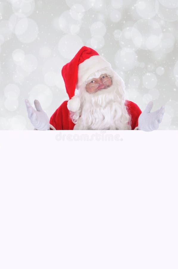 Santa Claus que faz um gesto com ambas as mãos como está atrás imagens de stock royalty free